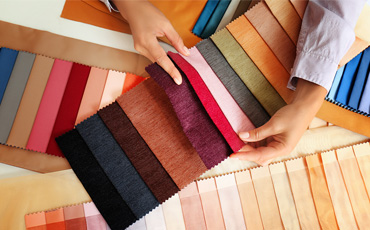 Shop assistant showing wide range of curtain colours