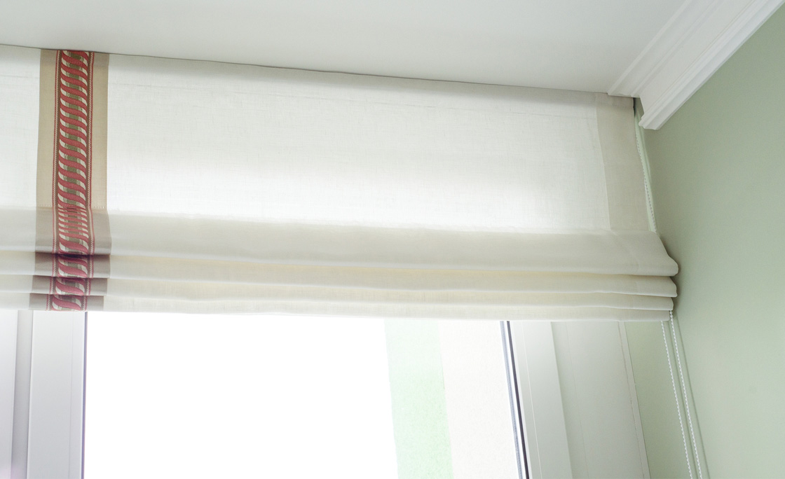 Traditional Roman blind raised up to create folded window covering