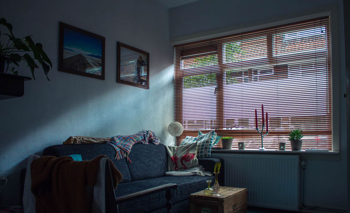 Stylish brown Venetian blind allows small amount of light to enter the room through its slats